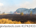Forest wildfire due to dry windy weather. Fire engine with firefighters handling flame, Blue sky 41742433
