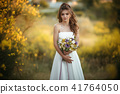 Beautiful young bride with fashion bouquet of wildflowers in yellow field, nature wedding concept 41764050