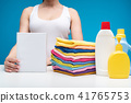 Woman standing at board with laundry liquids and clean garments 41765753