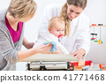 Pediatric care specialist smiling while measuring the weight of a baby girl 41771468