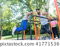 Two strong young men doing dips exercise for the upper body outdoors 41771536