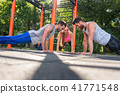 Two young men clapping hands from plank position during partner workout 41771548