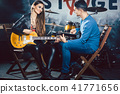 Woman taking guitar lessons with music teacher  41771656
