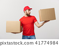 Delivery young man in red uniform holding two empty cardboard boxes isolated on white background 41774984