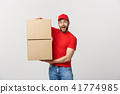 Delivery young man in red uniform holding two empty cardboard boxes isolated on white background 41774985