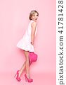 Young attractive blonde in short dress and in pink high heels posing seductively on pink . 41781428