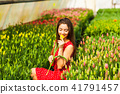 Young woman sitting in a red tulips field at sunset 41791457