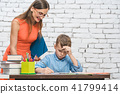 Student boy doing work in school supervised by his teacher 41799414