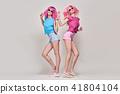 Two Girls Having Fun Dance. Pink Fashion Hairstyle 41804104
