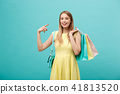 Beautiful young girl in yellow dress points to something with her finger 41813520