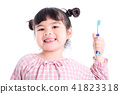 girl holding toothbrush and smiles over white  41823318