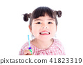 girl holding toothbrush and smiles over white  41823319