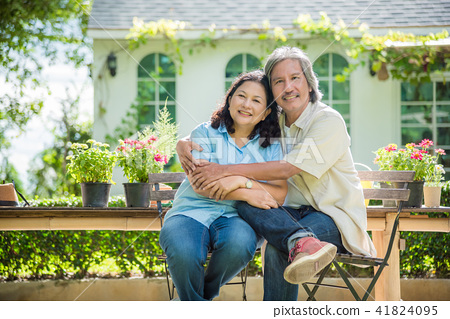 Retired couple sitting in front of their house  41824095