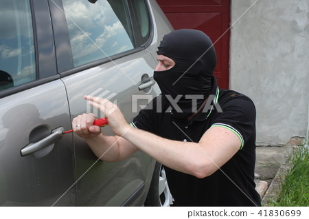 Car thief trying to break into a car with a screwd 41830699
