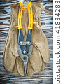 Pair of protective gloves wire cutter on wooden board 41834283