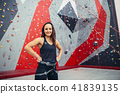 Portrait of happy woman with rope in fitness studio 41839135