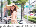 Young woman with public sharing bicycle in city 41840619