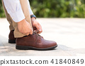 Businessman with leather shoes tying shoe laces 41840849