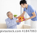 family celebrating and son giving gift to father 41847063