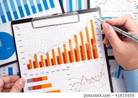 分析業務數據。收集統計數據。指向包含許多圖形的報告的手。 41855956