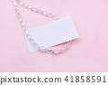 Crystal necklace and on pink wallpaper with paper. 41858591