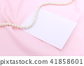 Pearl necklace on the pink fabric with paper note. 41858601