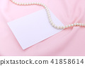 Pearl necklace on the pink fabric with paper note. 41858614
