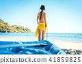 Woman dragging her boat to the water on the beach 41859825