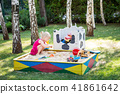 Little cute baby girl play in wooden sandbox. Child on sand playground among green lawn and birch 41861642