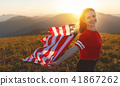 happy woman with flag of united states enjoying the sunset on na 41867262