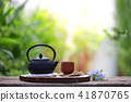 Old black tea pot with brown cup and flower 41870765