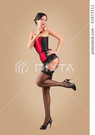 Lady in corset pressing her foot in stockings 41873511