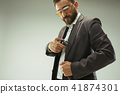 Businessman pulling the gun out of pocket 41874301
