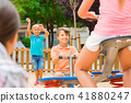 Cheerful children are teetering on the swing 41880247