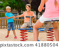 kids are teetering on the swing on the playground. 41880504