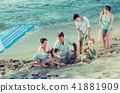 Smiling family with four children playing on sea beach 41881909