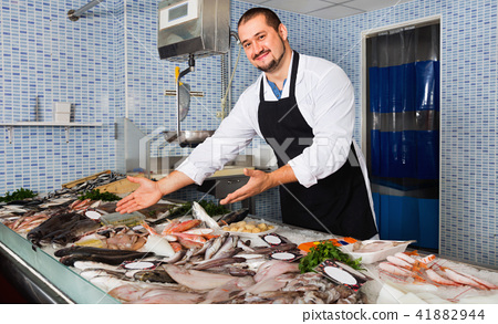 Seller in black apron showing fish on his counter 41882944