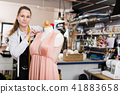 Woman worker measuring new dress at mannequin at atelier 41883658