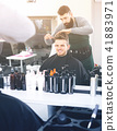 friendly guy stylist creating haircut for man client at hairdressing salon 41883971
