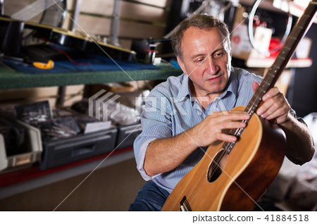 male is repairing music instruments 41884518