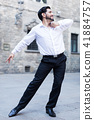 Young man dancing near old castle 41884757