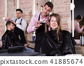 Brunette getting haircutting in salon 41885674