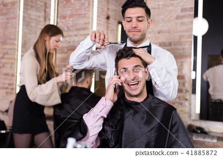 Cheerful man talking on phone in barbershop 41885872