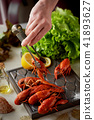 Boiled crayfish lie on a platter.Female hand holding tweezers and puts cancers. Fresh salad 41893627