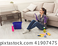 Screaming woman cleaning floor with lots of tools 41907475