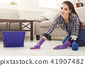 Smiling woman polishing wooden floor 41907482