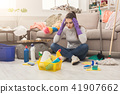Shocked woman cleaning house with lots of tools 41907662