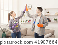 Couple giving five to each other holding cleaning equipment 41907664