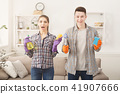 Young couple holding cleaning equipment at home interior background 41907666