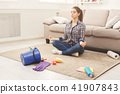 Woman meditating while cleaning home 41907843